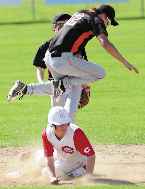 LOOK OUT: Skowhegan shortstop Kameron Wallace leaps out of the way of sliding Cony baserunner Mitchell Caron on Friday in Augusta.