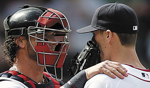 HONORING MOTHERS: With his finger nails painted pink for Mother's Day, Boston Red Sox catcher Jarrod Saltalamacchia, left, talks with relief pitcher Clayton Mortensen during the sixth inning against the Toronto Blue Jays on Sunday at Fenway Park in Boston.