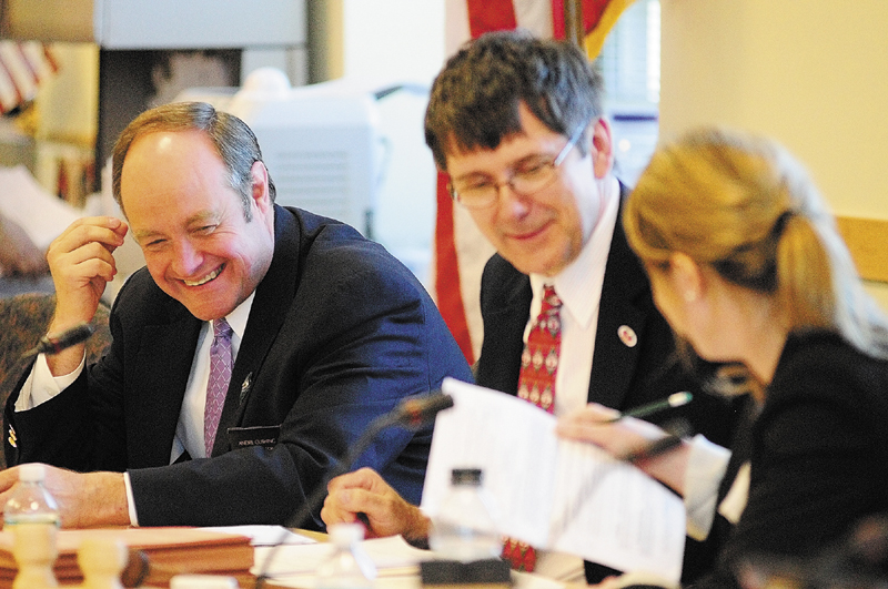 Sen. Andre Cushing, R-Hampden, left, confers with co-chairs Sen. John Patrick, D- Rumford, and Rep. Erin Herbig, D-Belfast, before a work session on L.D. 1230 on Friday in the Cross building in Augusta.