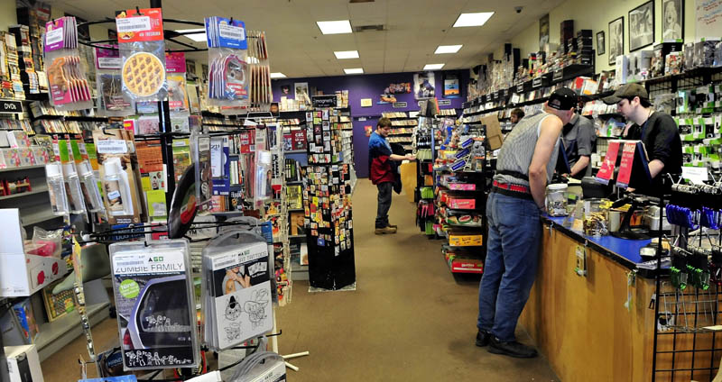 Bull Moose Music head clerk Aaron Beckim, right, waits on customer Arthur Ellis at the store in the Elm Plaza in Waterville. The business is expanding into the adjacent, former Mr. Paperback location.
