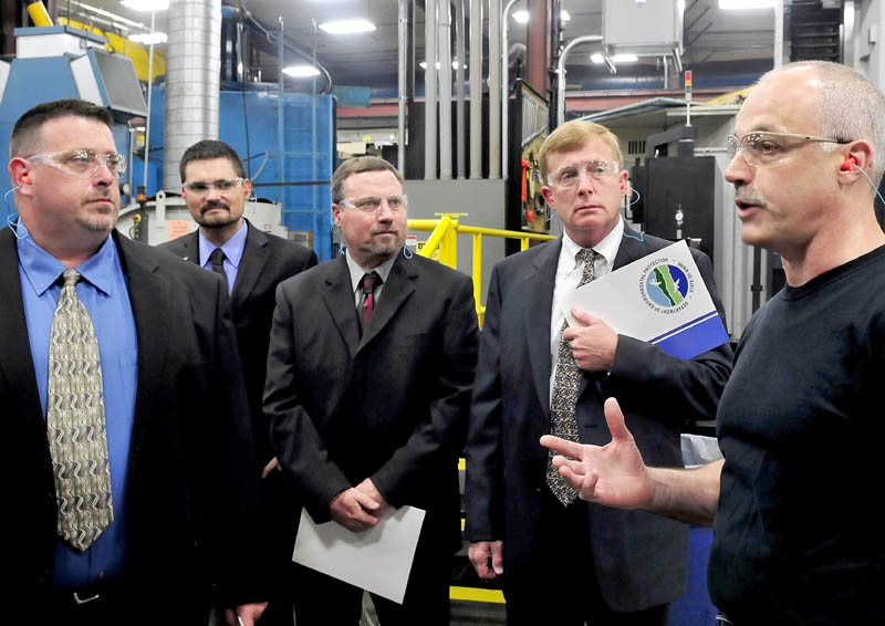 Mid-State Machine employee Steve Meunier, right, leads a tour through the Winslow company on Wednesday for a group with Edwards-United Technologies. The Pittsfield company was one of five businesses to receive a 2013 Environmental Excellence award from the state. From left are Bob Belanger, Steve LaMarre, Vern Palmer and Plant Manager Christopher Smith.