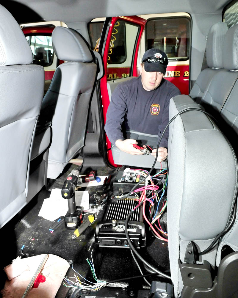 Lt. Tim Hardy connects radio equipment inside a new squad truck being assembled at the Farmington Fire Department. Several department personnel donated time and expertise to lower the cost of the new vehicle.