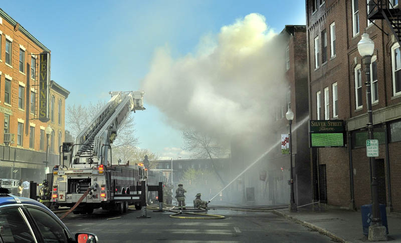 Firefighters spray water on a building on fire in downtown Waterville on Friday afternoon. The block is between Spring and Silver streets.
