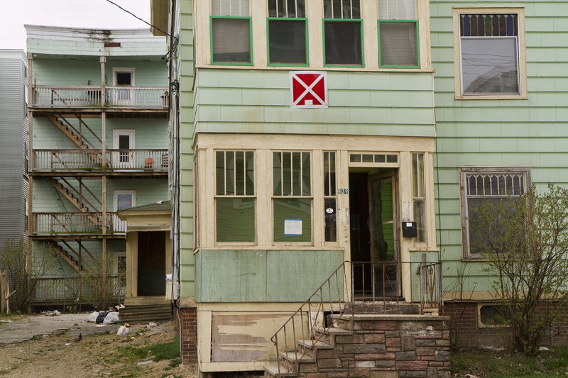 """The building at 139 Bartlett St. wears the signature red square with a white """"X,"""" designating it as a condemned property."""