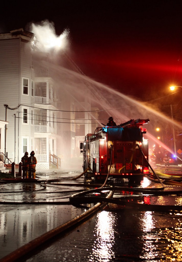 Early Saturday, firefighters train water toward the blazes that broke out in four buildings on Pierce and Bartlett streets in Lewiston. Fire investigators confirmed the fires started in a garage of a condemned property at 116 Pierce St.
