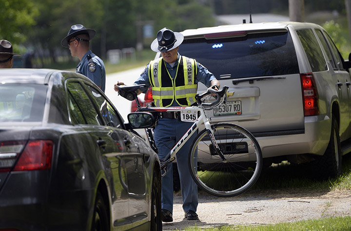 State police move a bike that was involved in a fatal crash in Hanover on Friday. David LeClair, 23, of Watertown, Mass., was struck by a tractor-trailer just miles from the starting point of the annual Trek Across Maine cycling event.
