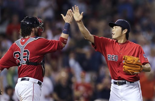 Boston Red Sox relief pitcher Koji Uehara, right, high-fives catcher Jarrod Saltalamacchia after final out of Boston's 7-5 win over the Toronto Blue Jays in a baseball game at Fenway Park, Friday, June 28, 2013, in Boston. Uehara earned a save in his outing. (AP Photo/Charles Krupa)