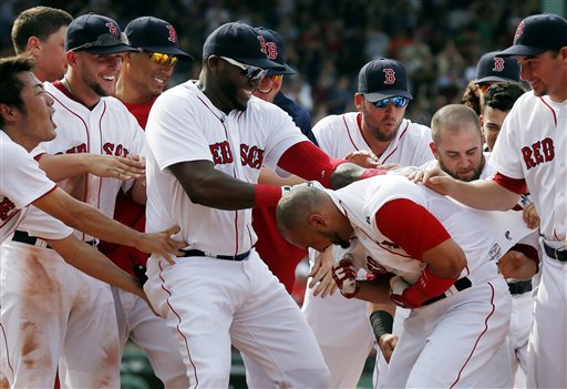 Teammates celebrate with Boston Red Sox outfielder Shane Victorino after reaching on a fielding error by Toronto Blue Jays first baseman Josh Thole, allowing Jonathan Diaz to score in the ninth inning Sunday at Fenway Park in Boston. The Red Sox won 5-4.