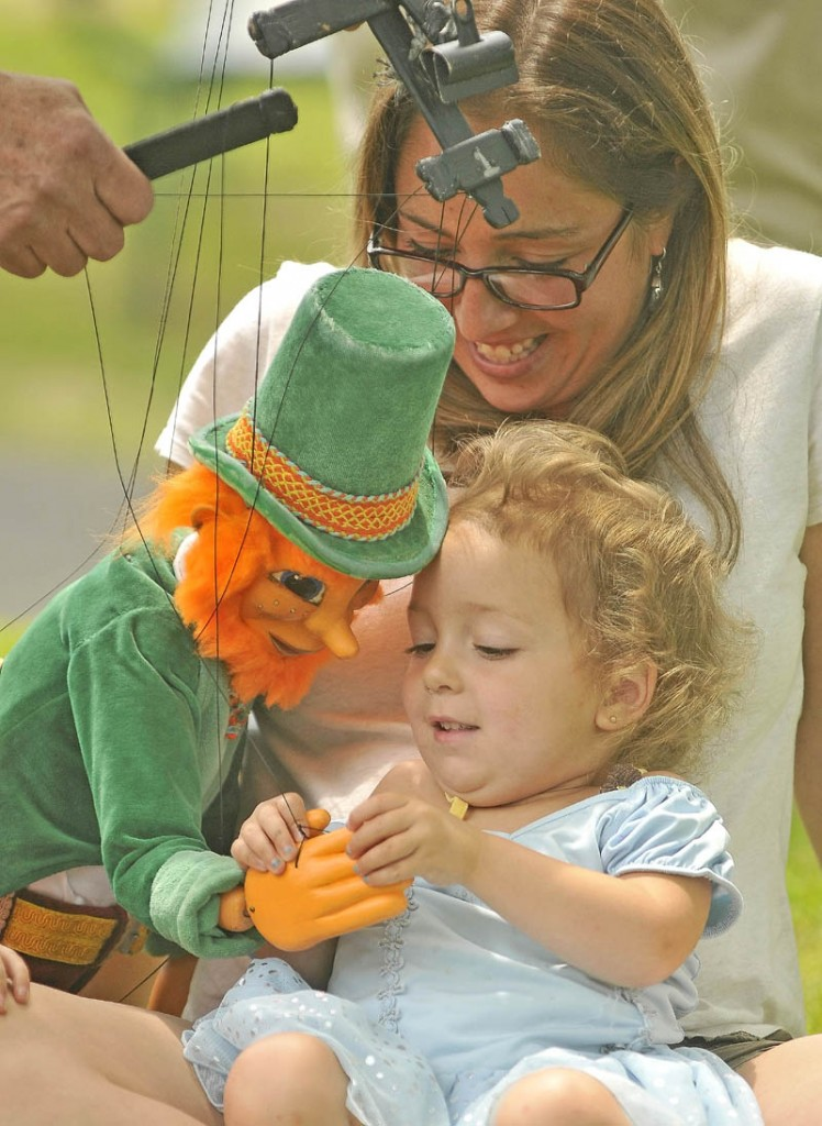 Meadow Bean, 2, and her mother, Josie Bean, enjoy puppeteer Dan Grady's leprechaun marionette at the first Summer Solstice Celebration in downtown Farmington on Saturday.