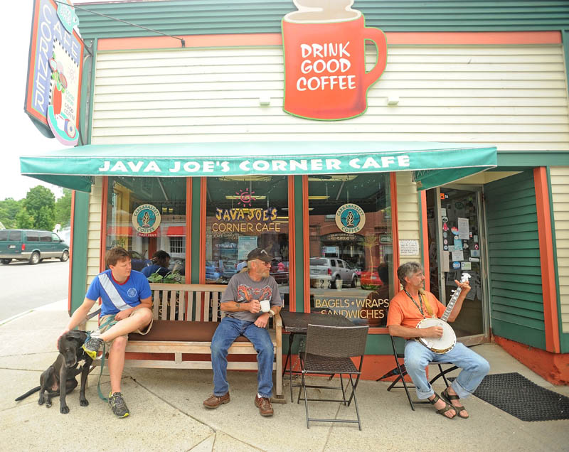 Pep Stevens, 52, right, picks his banjo outside Java Joe's Corner Cafe as Jay Heyse, center, and Zach Lopez, left, listen over a cup of coffee at the first Summer Solstice Celebration in downtown Farmington on Saturday.