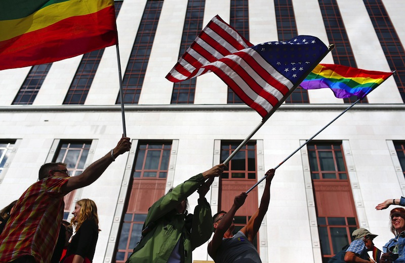 People wave American and gay pride flags outside the old Federal Courthouse in downtown Seattle on Wednesday, June 26, 2013, to celebrate the striking down of the Defense of Marriage Act by the Supreme Court. (AP Photo/The Seattle Times, John Lok)