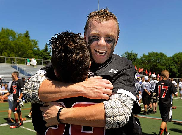 A smiling Austin Doody hugs teammate Luke Bernard after Scarborough won its fourth straight Class A state championship.