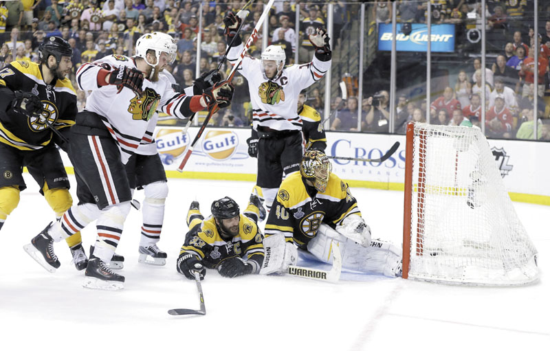 HEART-BREAKING GOAL: Chicago Blackhawks left wing Bryan Bickell, left, celebrates his goal against the Boston Bruins, with Blackhawks center Jonathan Toews, center, as Bruins defenseman Zdeno Chara (33) and goalie Tuukka Rask (40) watch the puck in the goal during the third period of Game 6 of the Stanley Cup finals on Monday in Boston. Chicago scored two goals in 17 seconds, the second with less than a minute to go, to beat the Bruins 3-2 and win the Stanley Cup. TD Garden