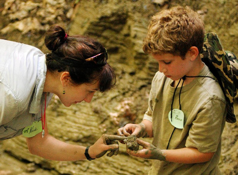 Nicole Rhodes, left, and Rocco Landry, 8 of Lewiston, take a closer look at clay they found along the banks of a stream in the Small-Burnham Conservation Area on Tuesday in Litchfield.