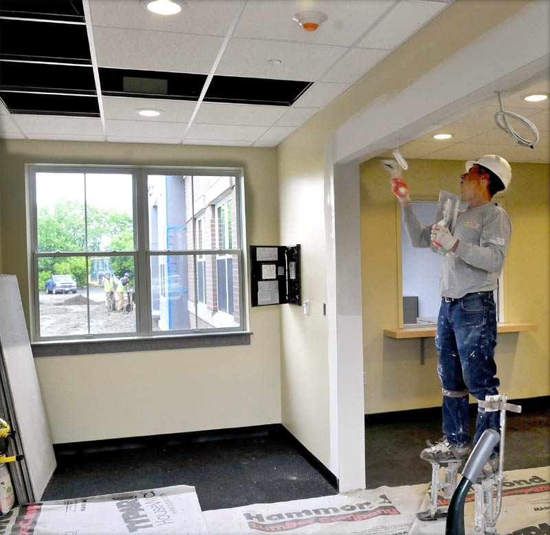 Dan Poirier tapes the ceiling at the entrance to the new Waterville police station on Wednesday.