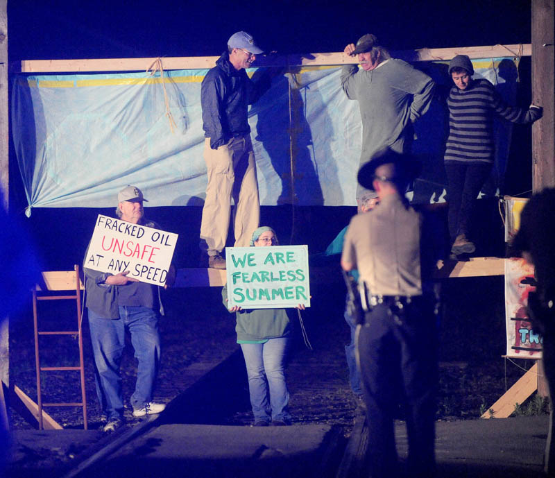 Protesters from 350 Maine block the railroad crossing at Lawrence Avenue in Fairfield Thursday night, to protest the transport of fracked oil.