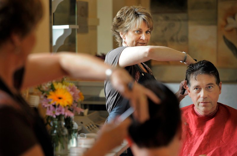 """Gabe Souza/Staff Photographer Holly Fent, shown cutting the hair of Peter McDonald of Scarborough at Hair It Is on St. John Street, recognizes that she can be a trusted """" sounding board,"""" but technology has eroded the personal touch that helped protect privacy for the previous two centuries."""