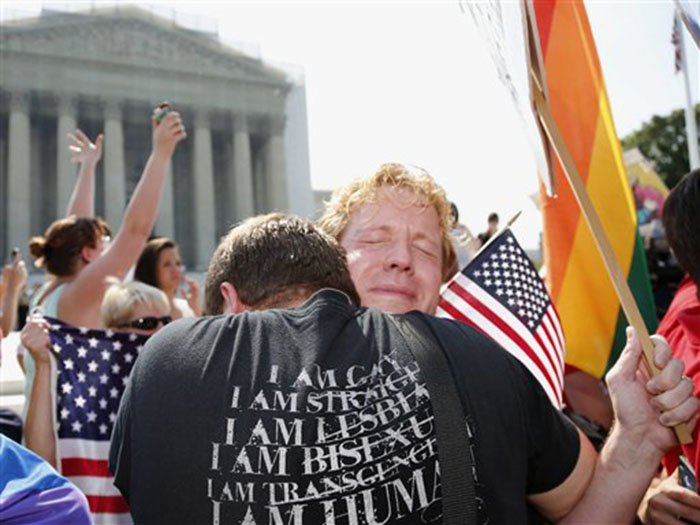 Michael Knaapen, left, and his husband John Becker, right, embrace outside the Supreme Court in Washington on Wednesday after the court struck down a federal provision denying benefits to legally married gay couples.