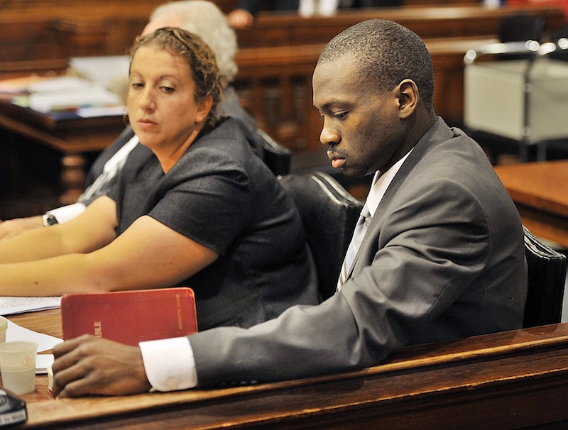 Assistant defense attorney Tina Nadeau looks on as Eric Gwaro, accused of beating a woman and causing her permanent brain damage, looks at his Bible on Friday, July 26, 2013. Friday was the last day of testimony and closing arguments in Gwaro's trial.