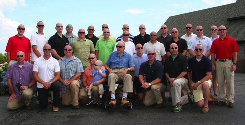 President George H.W. Bush, center, dons trademark sunglasses to pose with a Secret Service group after they shaved their heads in support of a 2-year-old boy being treated for leukemia, left of Bush. This photo was shared on Twitter by Jim McGrath, Bush's spokesman.