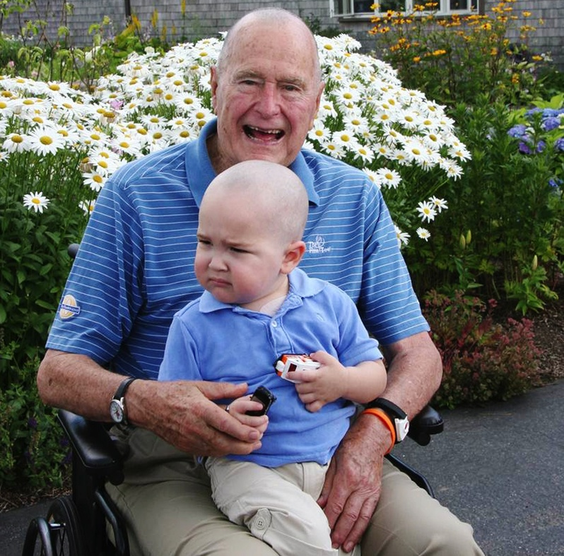 Former President George H. W. Bush sits with Patrick, 2, whose last name was withheld at the family's request, in Kennebunkport on Wednesday. Bush joined members of his Secret Service detail in shaving his head to show solidarity with Patrick, who is undergoing treatment for leukemia and is losing his hair as a result.