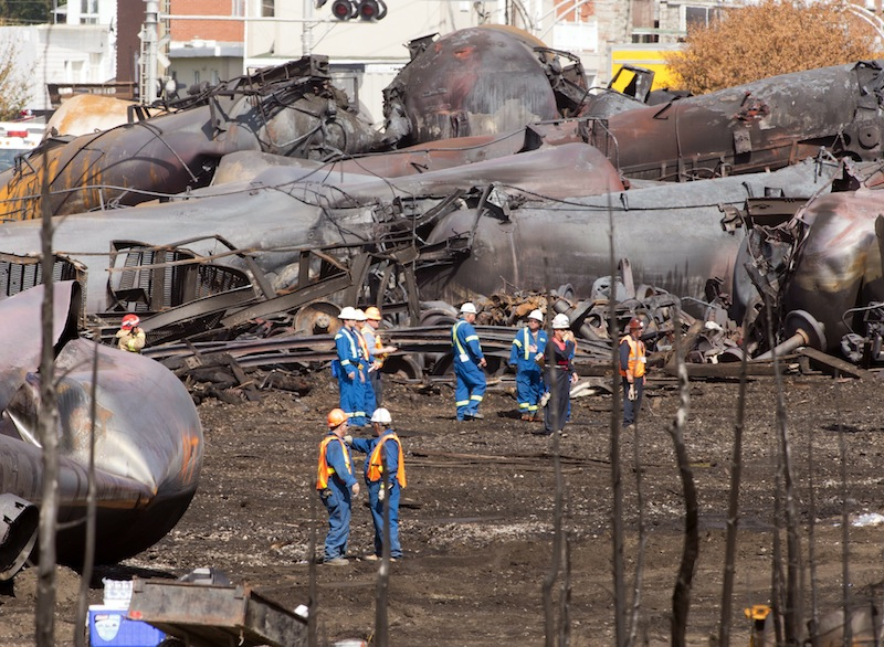 Workers stand before mangled tanker cars Tuesday, July 16, 2013, at the crash site of the train derailment and fire in Lac-Megantic, Quebec. The July 6, 2013, accident left 50 people confirmed dead. (AP Photo/Ryan Remiorz, pool)