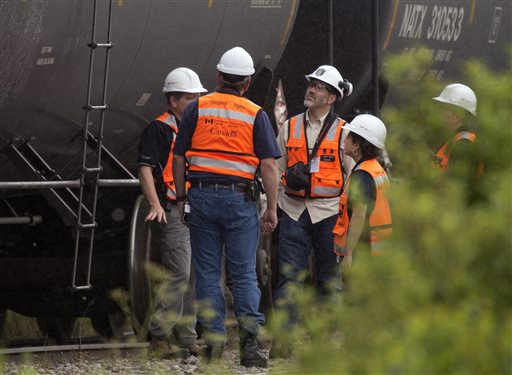 Environment Canada emergency inspectors check on nine MM&A tanker cars that remain on the tracks in Nantes, Quebec, Wednesday. A train engineer reportedly rushed to borrow a tractor from an area forestry company; grabbed a fireman's suit from an area department; and pushed nine fuel-filled cars weighing 100 tons away from the explosive danger on the night of the derailment, according to the company.