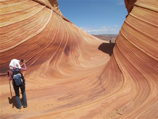 This May 28, 2013, photo shows a hiker taking a photo on a rock formation known as The Wave in the Vermilion Cliffs National Monument in Arizona. The flowing sandstone rock formation near the Utah-Arizona border that claimed the lives of a California couple earlier this month.