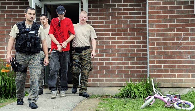 Augusta Police officers escort Matthew Jepsen, 29, of Augusta on Monday from an apartment in Augusta they raided with drug agents. Several individuals were arrested on drug charges, according to police.