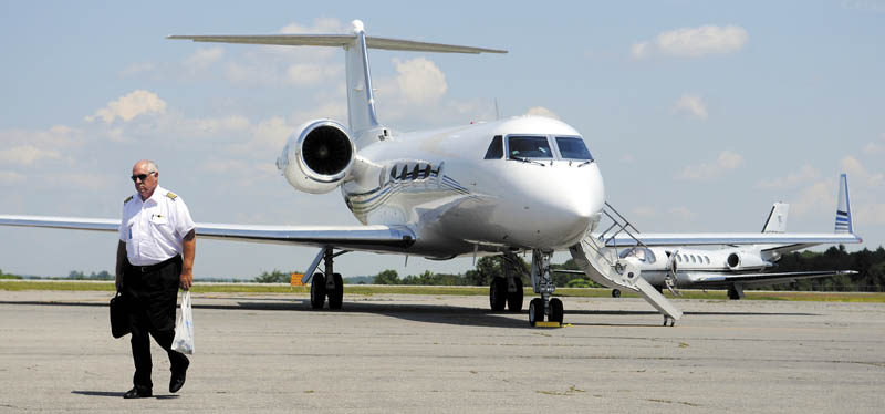 A pilot walks past two private jets July 16 near Maine Instrument Flight at the Augusta State Airport. Maine Instrument Flight owner William Perry said more jets are arriving earlier to visit summer campers than previous years.