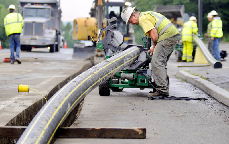 Workers with Bowdoin Excavation lay gas pipes Tuesday in Augusta for Maine Natural Gas, which recently signed the University of Maine at Augusta as a client.