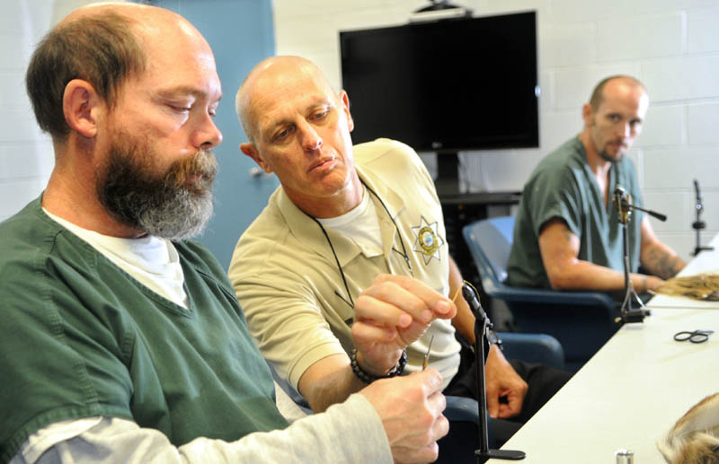 Inmates Chris Ring, left, and Jared Small, right, learn to tie fishing flies with corrections Sgt. Alan Gregory Tuesday, in a conference room at the Kennebec Country Correctional Facility in Augusta. The veterans are serving time together on the same cell block. A fly-fishing guide and veteran, Gregory said the men are being taught to tie the flies to learn a new skill that may earn them money.