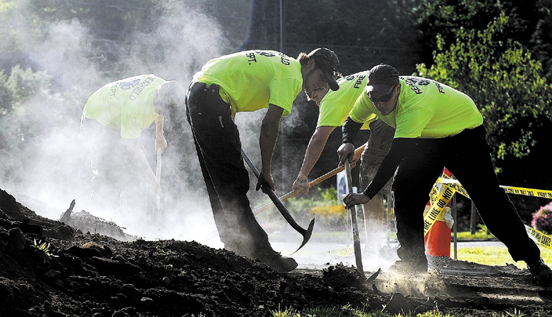 Readfield firefighters shovel dirt of the top of steel plates covering their bean hole beans in 2011 during Readfield Heritage Days. Readfield's bean hole supper is Saturday from 4:30 to 6 p.m. at the Readfield fire station.