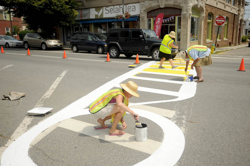 Pat Burdick, foreground, paints a new Maine International FIlm Festival themed cross walk on Main Street downtown in Waterville on Sunday. Assisting Burdick is Kevin James, back right, and Jennifer Olsen, executive director for Waterville Main Street.