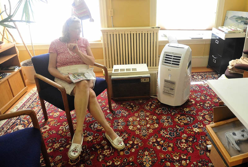 Jennifer Kierstead sits next to her brand new energy efficient air conditioner that is replacing the older air conditioner in her downtown Waterville office on Tuesday. As temperatures rise, Central Maine Power is asking customers to limit their power usage.