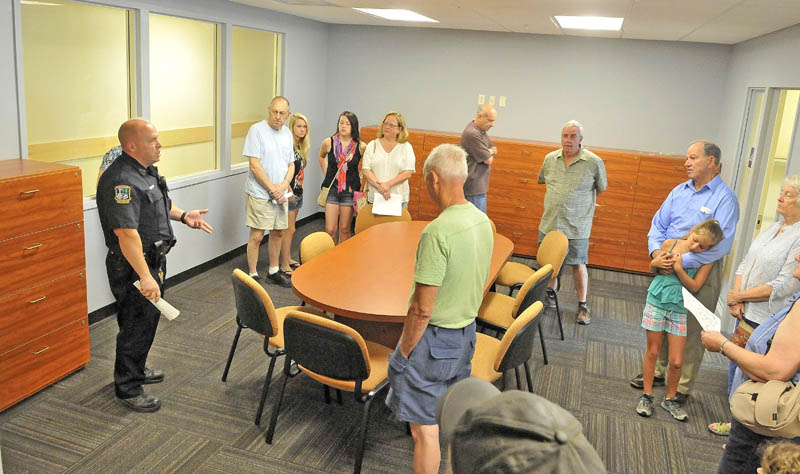Officer Dennis Picard gives a tour to the public during an open house at the new Waterville police station on Colby Circle Thursday morning.
