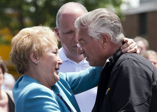 Raymond Lafontaine, who lost his son and two daughters-in-law, receives a hug from Quebec Premier Pauline Marois during her visit to Lac-Megantic, Quebec on Thursday, as Marois toured the site where a runaway oil train killed 50 people in a fiery explosion.