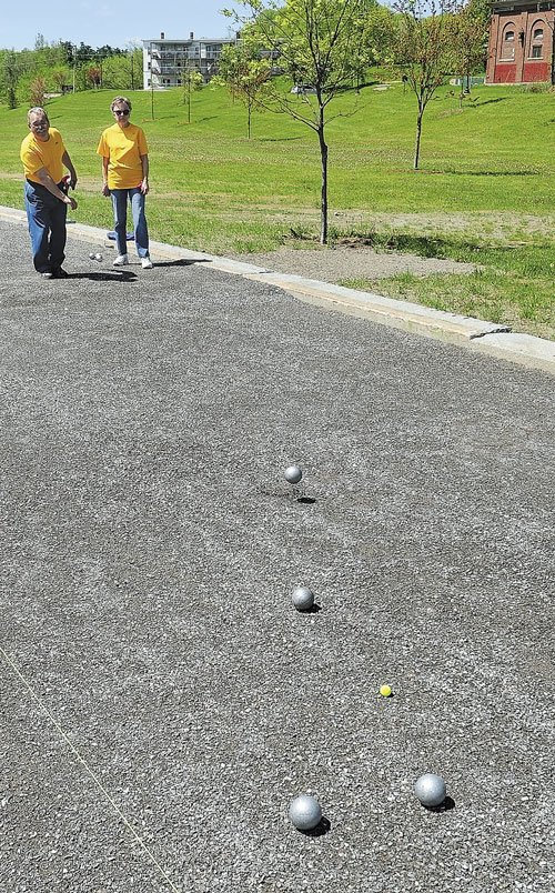 THIS IS HOW: Ray, left, and Lucette Fecteau demonstrate how to play pétanque at Mill Park in Augusta. The couple will host a tournament Sunday at the park.