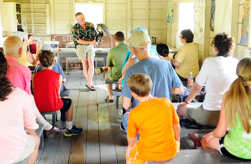 Falconer Larry Barnes talks about a Peale's peregrine falcon that he hunts ducks with in the winter, during a talk on Saturday in the boat house at the Steve Powell Wildlife Management Area, on Swan Island between Richmond and Dresden.