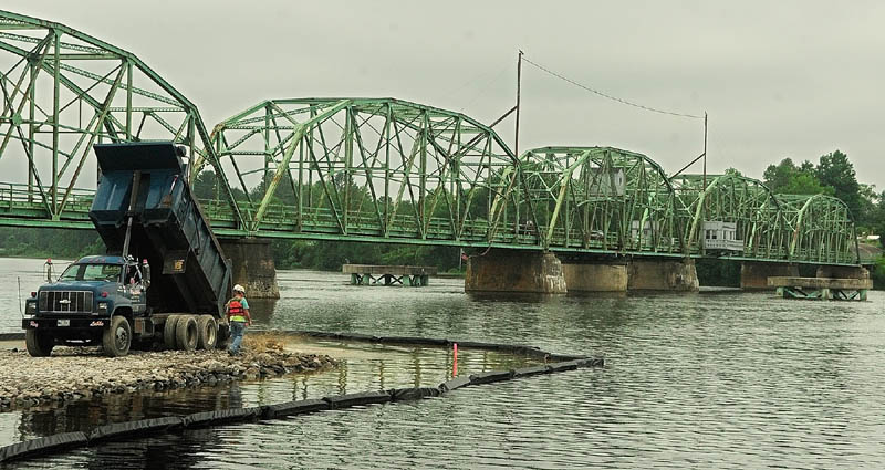 Reed & Reed Construction workers build a construction causeway on the Kennebec River Wednesday.