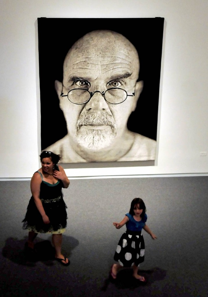 Mary Bedard, left, and Emma Alley walk past a self portrait tapestry by Chuck Close during one of many tours at the Colby College Museum of Art in Waterville on Sunday. The event was part of the museum Community Day.