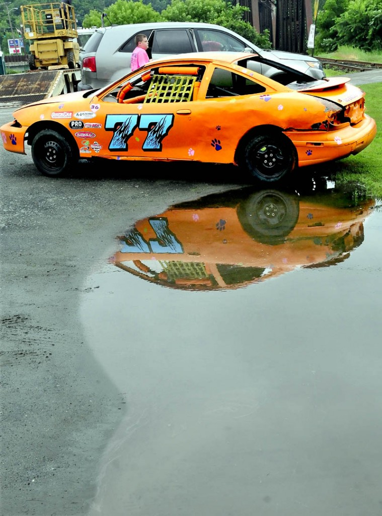 A race car is parked in a large puddle near Fort Halifax Park in Winslow on a wet Tuesday. The car is part of the Winslow Family 4th of July's