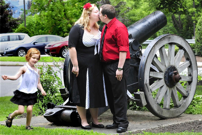 Newlyweds Erica and David Tompkins kiss beside a cannon in Castonguay Square in Waterville, moments after they were married in a civil ceremony, on Monday. Their daughter, Christina, runs around the couple as family members take photographs.
