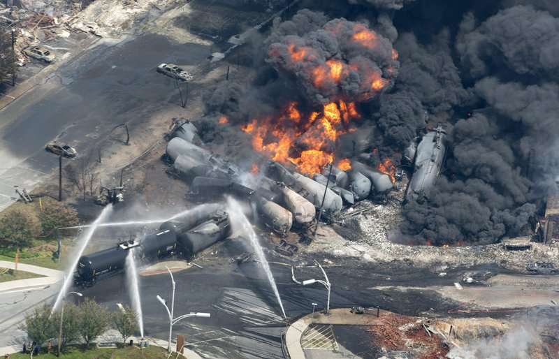 In this July 6 photo, flames and smoke rise from railway cars that were carrying crude oil after derailing in downtown Lac Megantic, Quebec, Canada, devastating the downtown and killing 47.