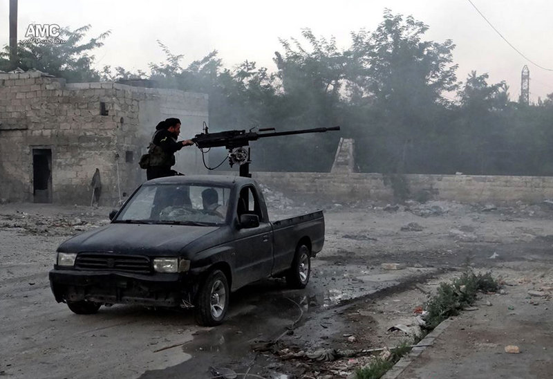 A Syrian rebel fires a heavy machine gun toward Syrian soldiers loyal to President Bashar Assad in Aleppo last month. Rebel forces have been falling back.