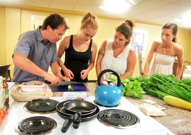 Tim Fuller, a health promotion specialist, demonstrates proper food chopping techniques at McAuley Residence.