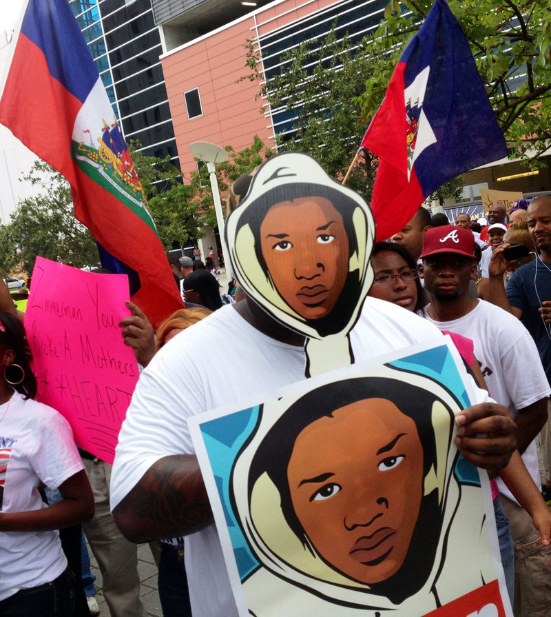 """Aqua Etefia holds signs during a """"Justice for Trayvon"""" rally in Miami on Saturday. The Rev. Al Sharpton's National Action Network organized rallies nationwide to press for federal civil rights charges against George Zimmerman."""
