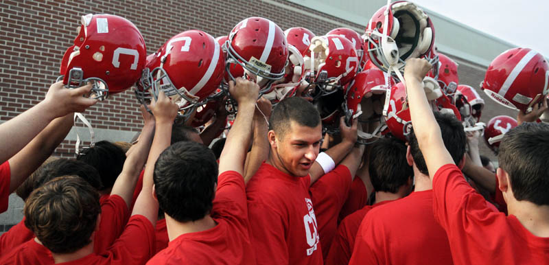 GOOD DAY: Cony High School quarterback Ben Lucas, center, raises his helmet with teammates on Monday during the first morning of football practice.