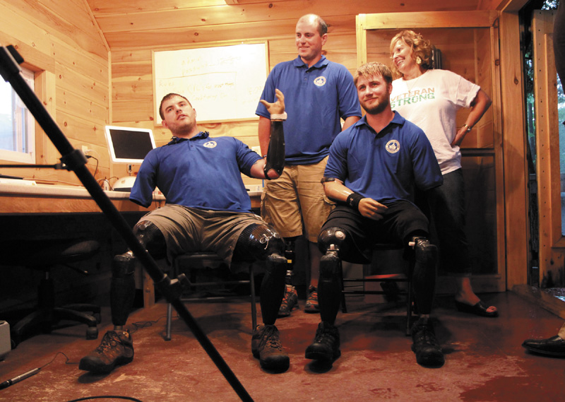 Quadruple amputee Travis Mills, left, talks to reporters with fellow wounded veterans Taylor Morris, right, and Drew Mullee, top, as Maine's First Lady Ann LePage looks on at Camp Kennebec in Belgrade on Wednesday night. This week is
