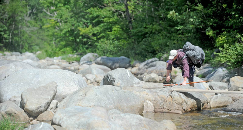 Jonathan Eaton, 54, of Warrenton, Va., crosses the Carrabassett River while thru-hiking the Appalachian Trail, in Wyman Township on Thursday. This section of trail intersects Route 27 in Wyman Township, where missing Tennesse hiker Geraldine Largay was scheduled to meet her husband, George, on July 24. She never made it for the scheduled rendezvous.